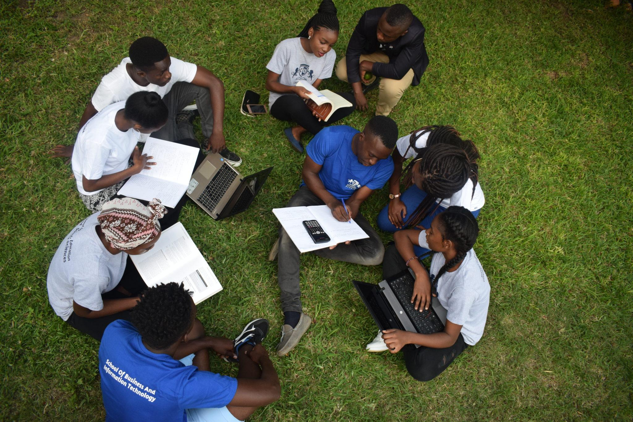 Students sitting outside on the ground and studying.