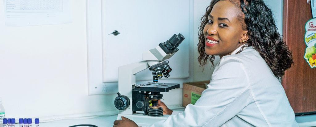 Kuvassa Penda Healthin laboratoriotyöntekijä työskentelee mikroskoopin äärellä