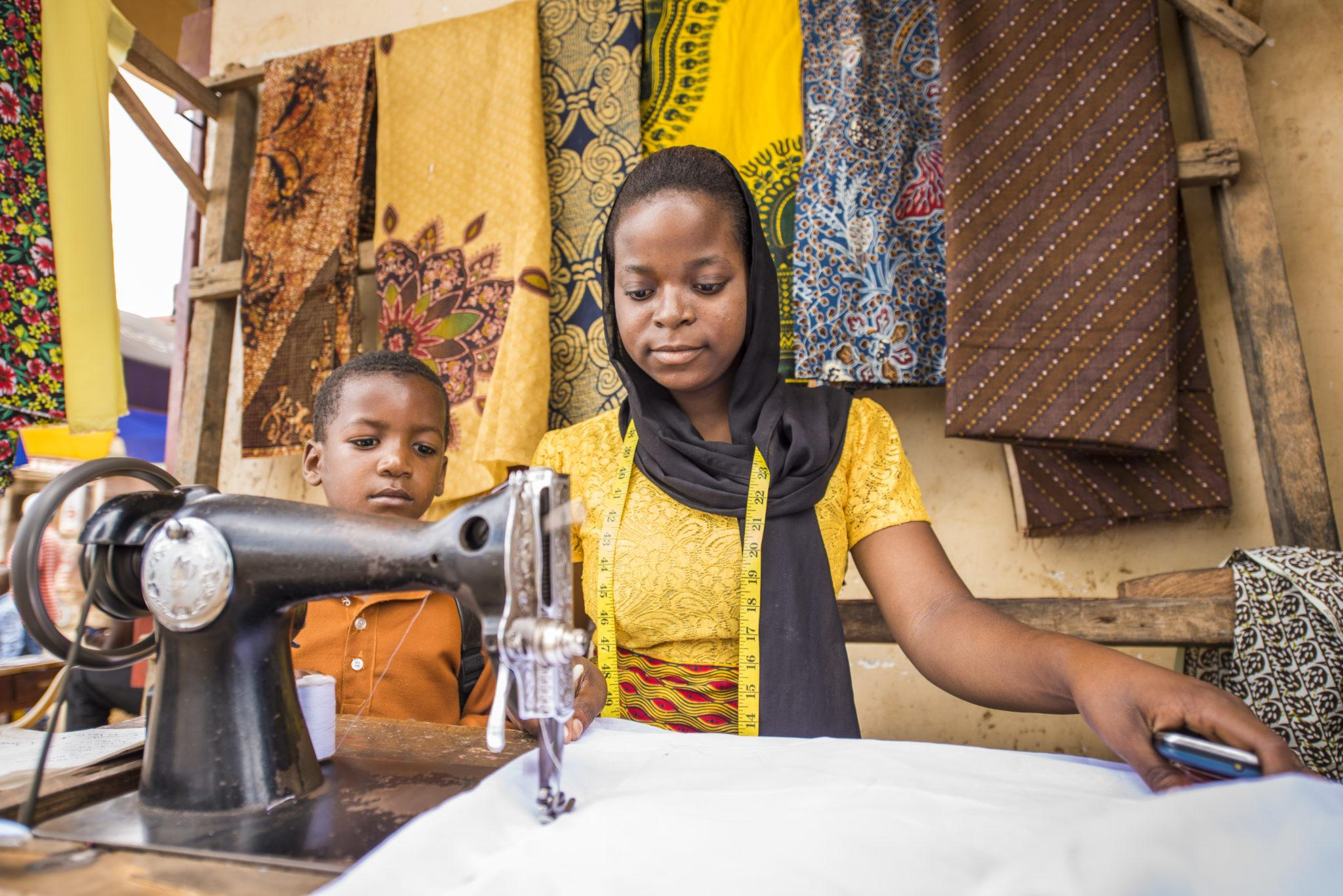 Person using a sewing machine and a child standing behind the person