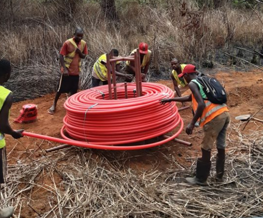 Men installing cable under the ground